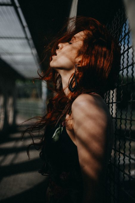 Photo of a woman leaning on a chain-link fence with her chin up