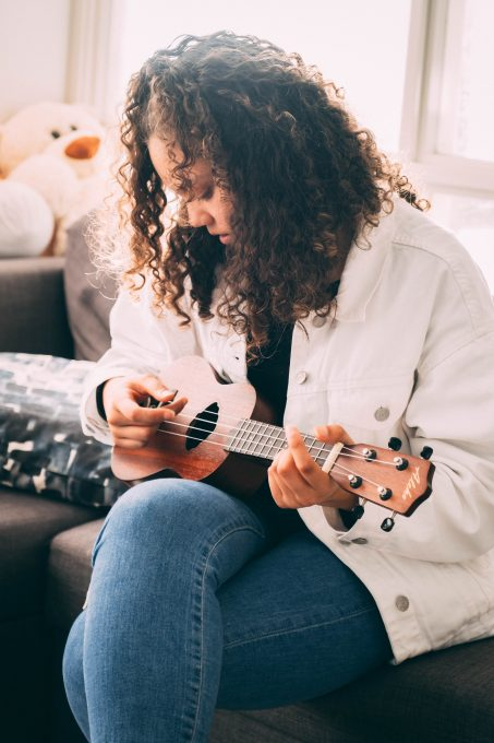 Photo of a woman playing ukulele sitting on a gray sofa