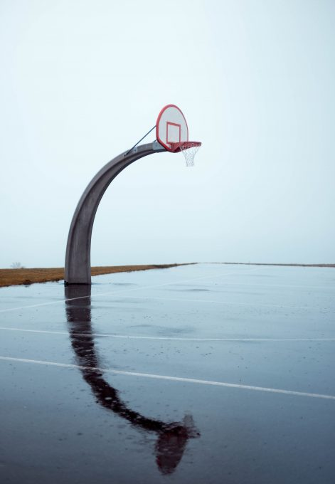 Photo of an empty concrete basketball court on a gloomy day