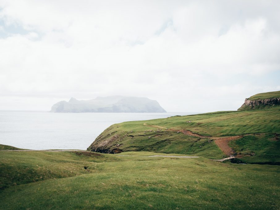 Photo of green fields by the water