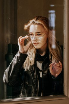 Portrait of a woman wearing a black leather jacket in front of a window