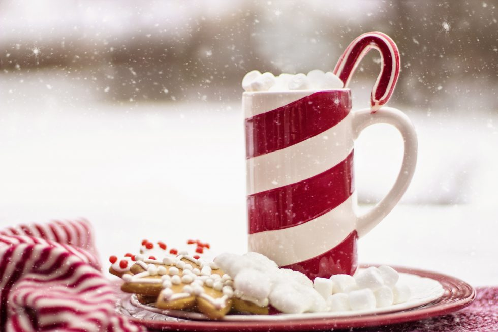 Snow falling on a mug with marshmallows and Christmas cookies on a plate