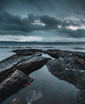 The body of water near rocks on a cloudy day
