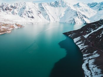 The calm body of water by snow-capped mountains