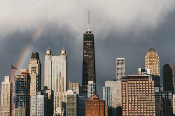 The rainbow stretching over high-rise buildings of a city