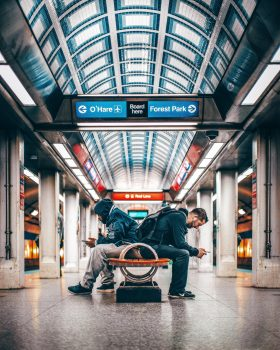 Two men sitting on a bench inside a station