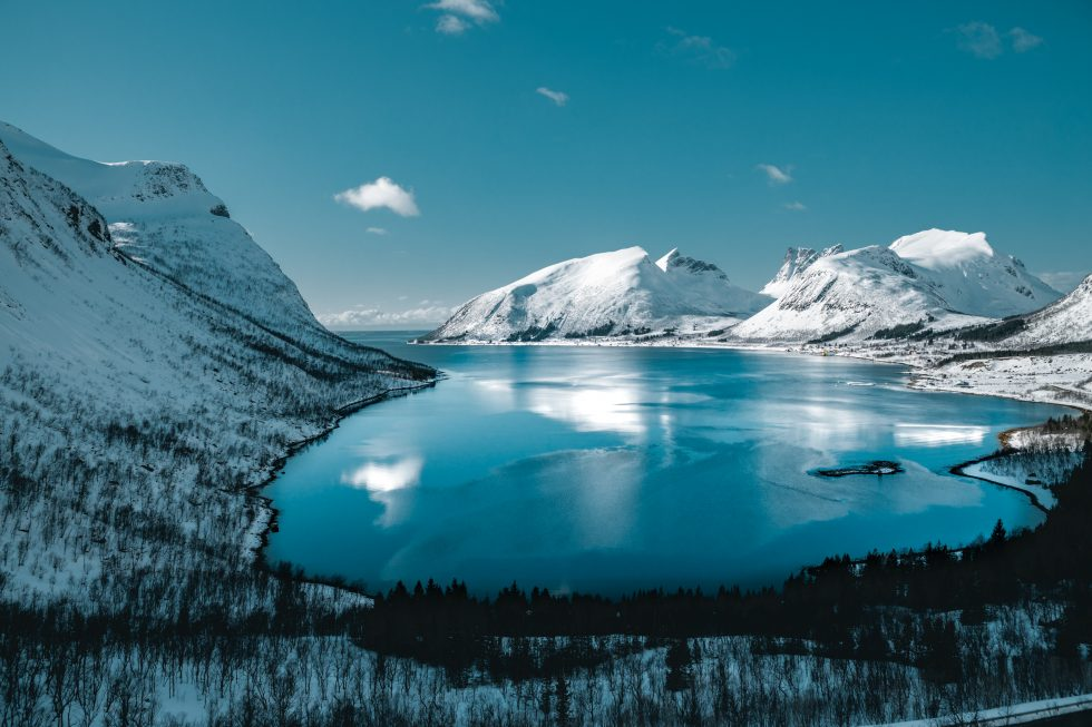 A lake surrounded by snow-covered mountains under a blue sky