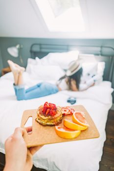 A person holding breakfast on a cutting board in front of a woman lying on a bed