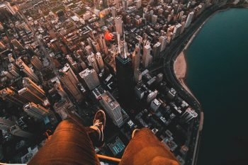 A person sitting on the roof of a skyscraper