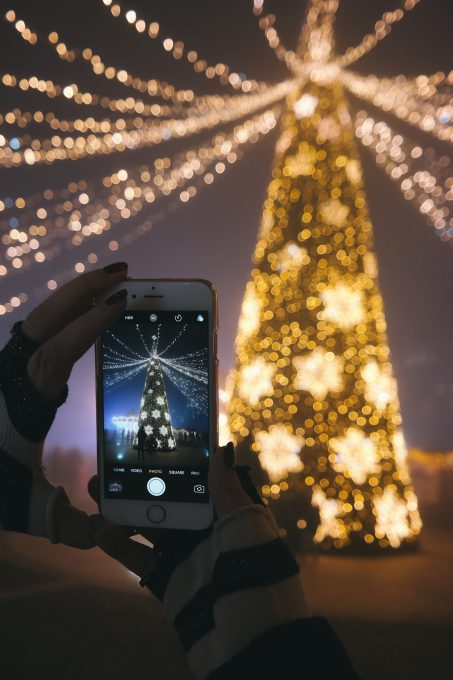 A person taking a picture of an illuminated Christmas tree