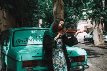 A woman playing the violin while leaning on a green car