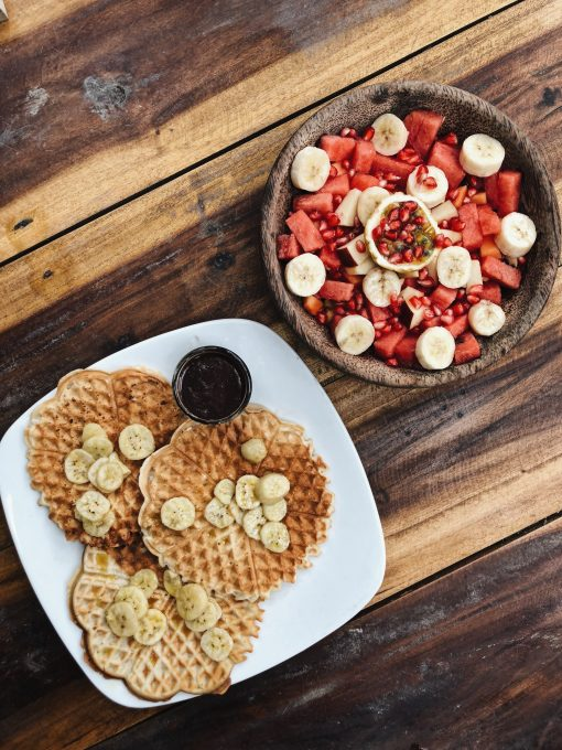 Flat lay of waffles and fruit salad