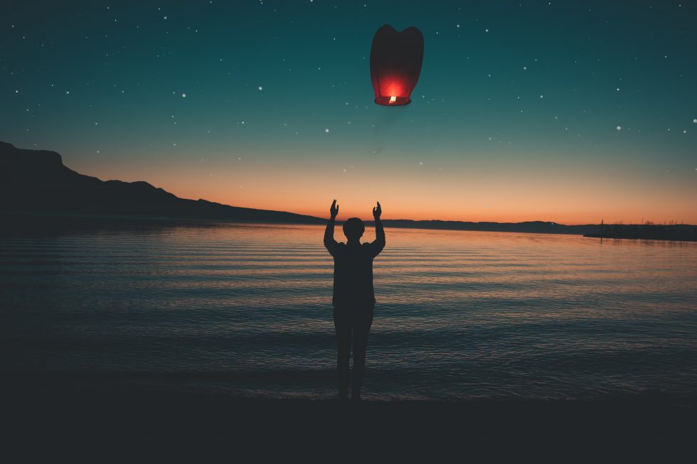 Silhouette of a person releasing a red paper Japanese lantern