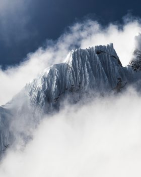 Snow-сovered mountain surrounded by clouds