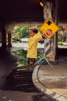 A boy jumping from the road curb