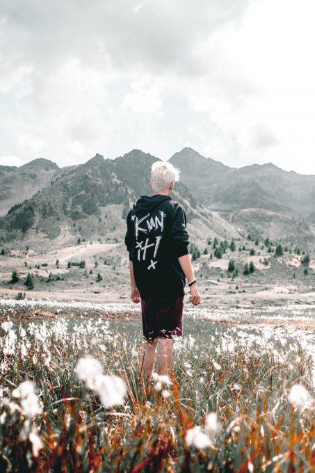 A man in a black top facing a mountain