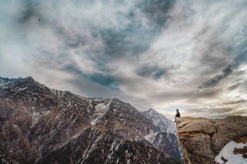 A man sitting on a mountain peak