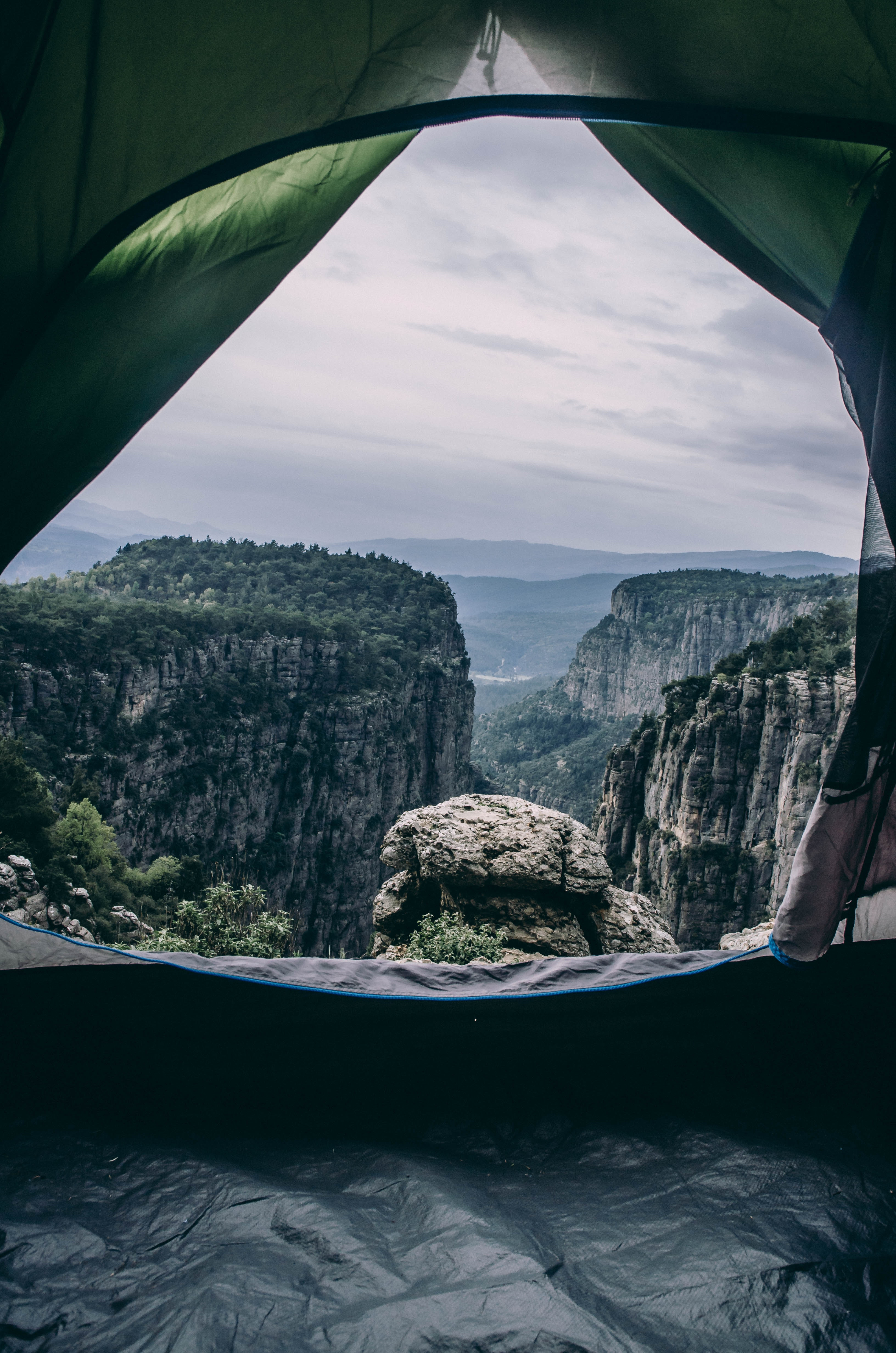 A person inside a dome tent on a cliff