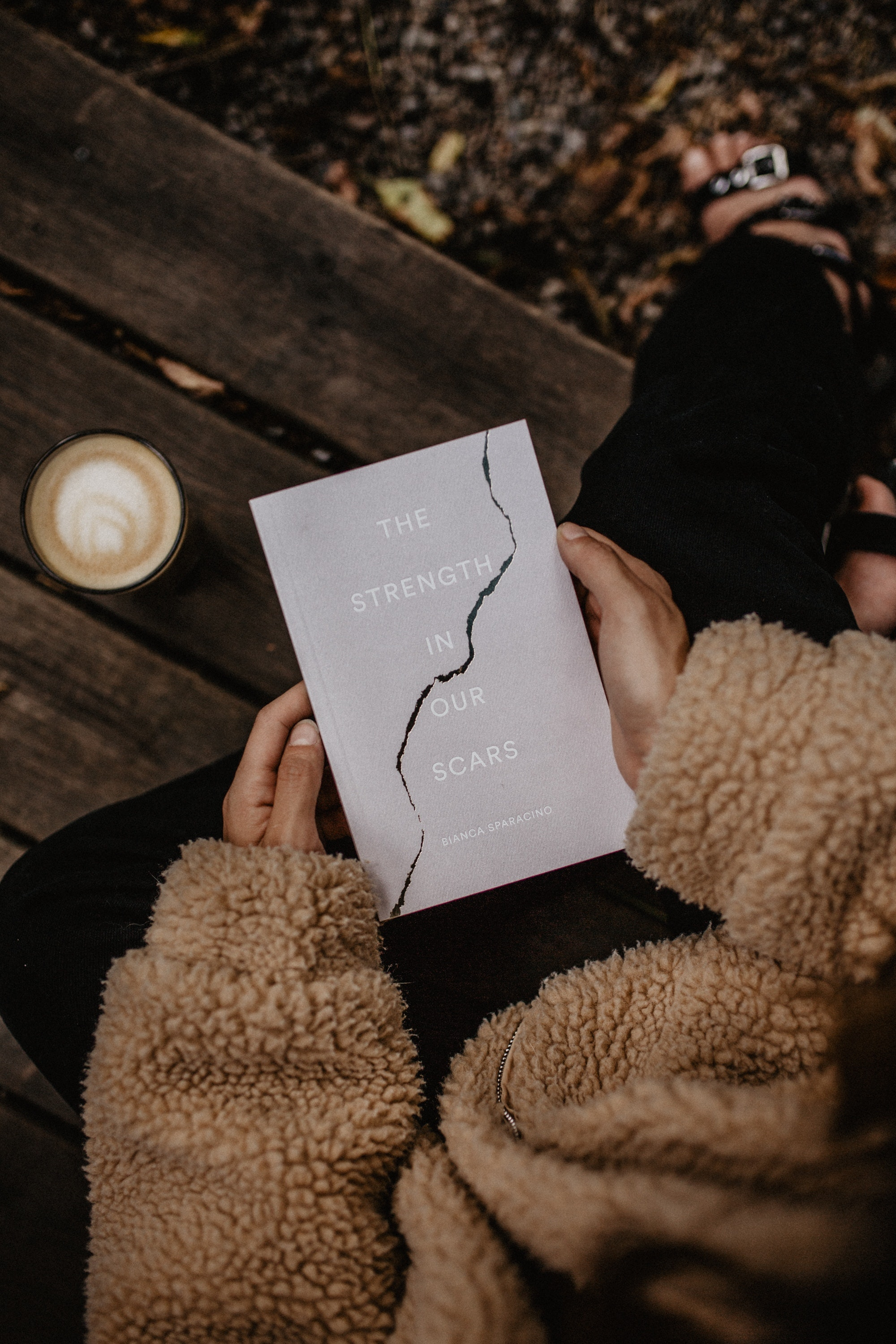 A person sitting on a bench holding a book