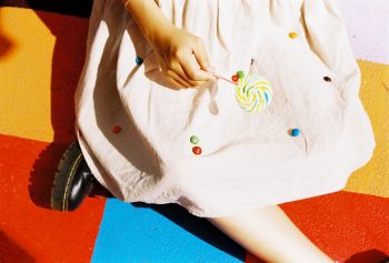 A person sitting on the colorful floor holding a lollipop