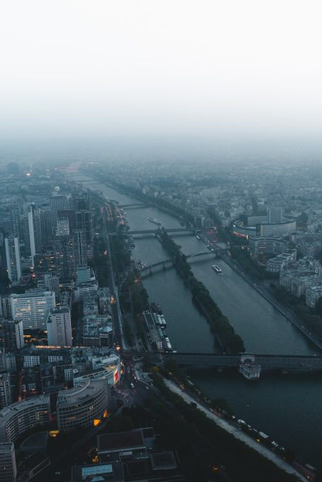 A river in the middle of a foggy city