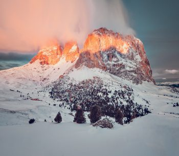 A rocky mountain covered with snow during golden hour