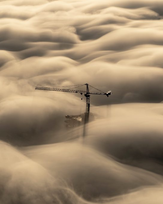 A tower crane above the clouds