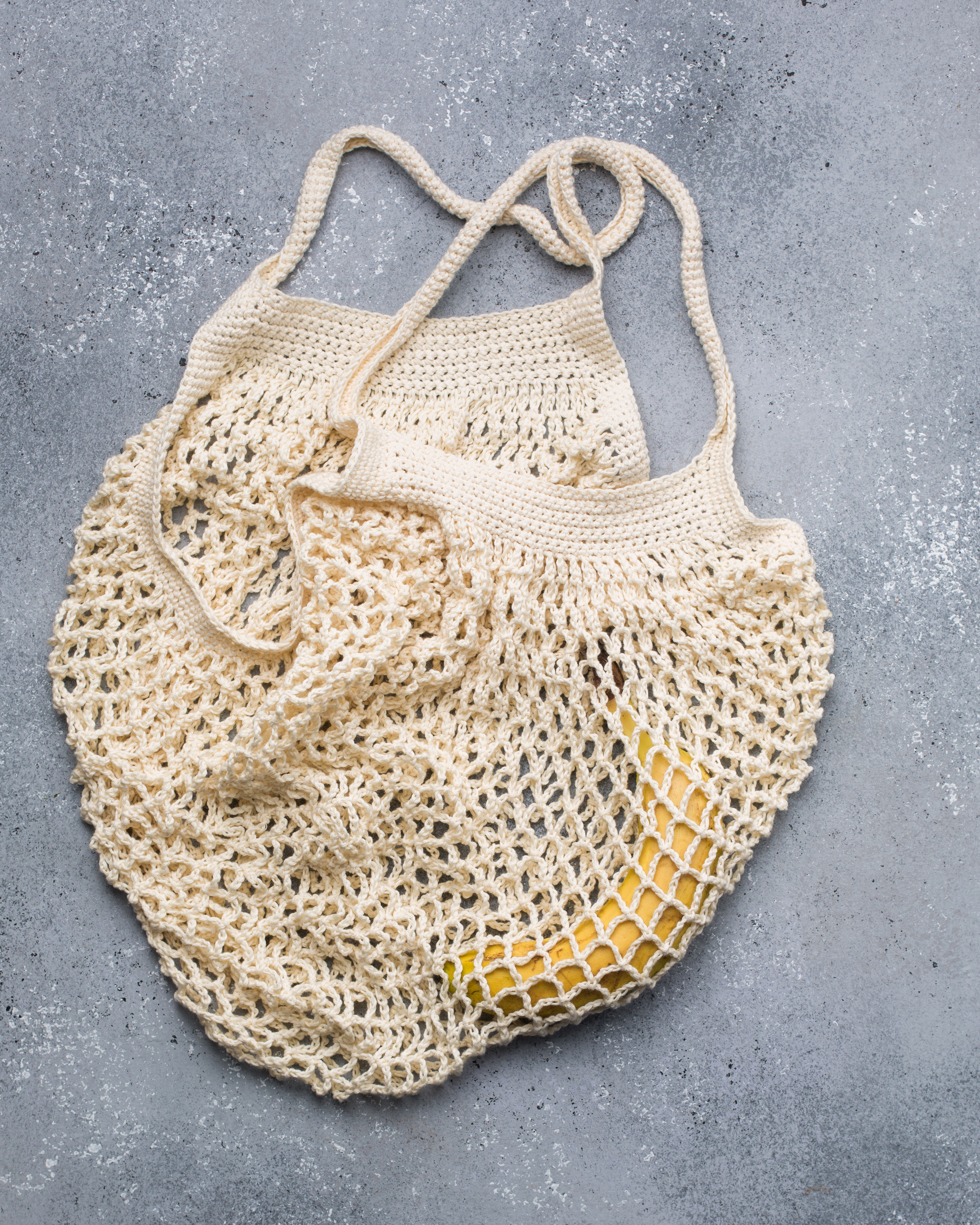 A white crocheted bag with a banana