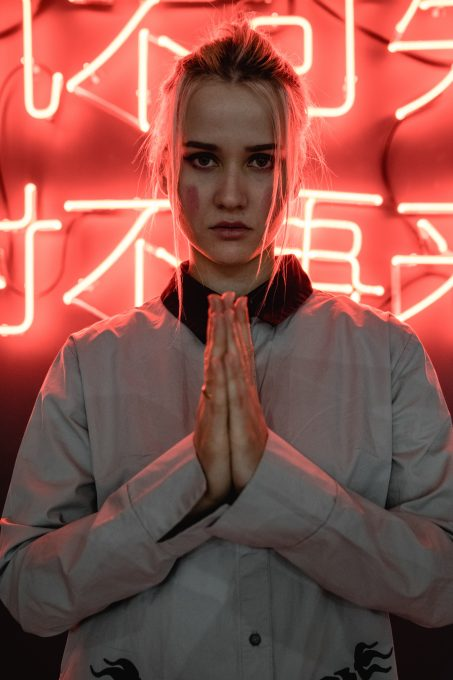 A woman making a praying hand sign in the background of neon signs