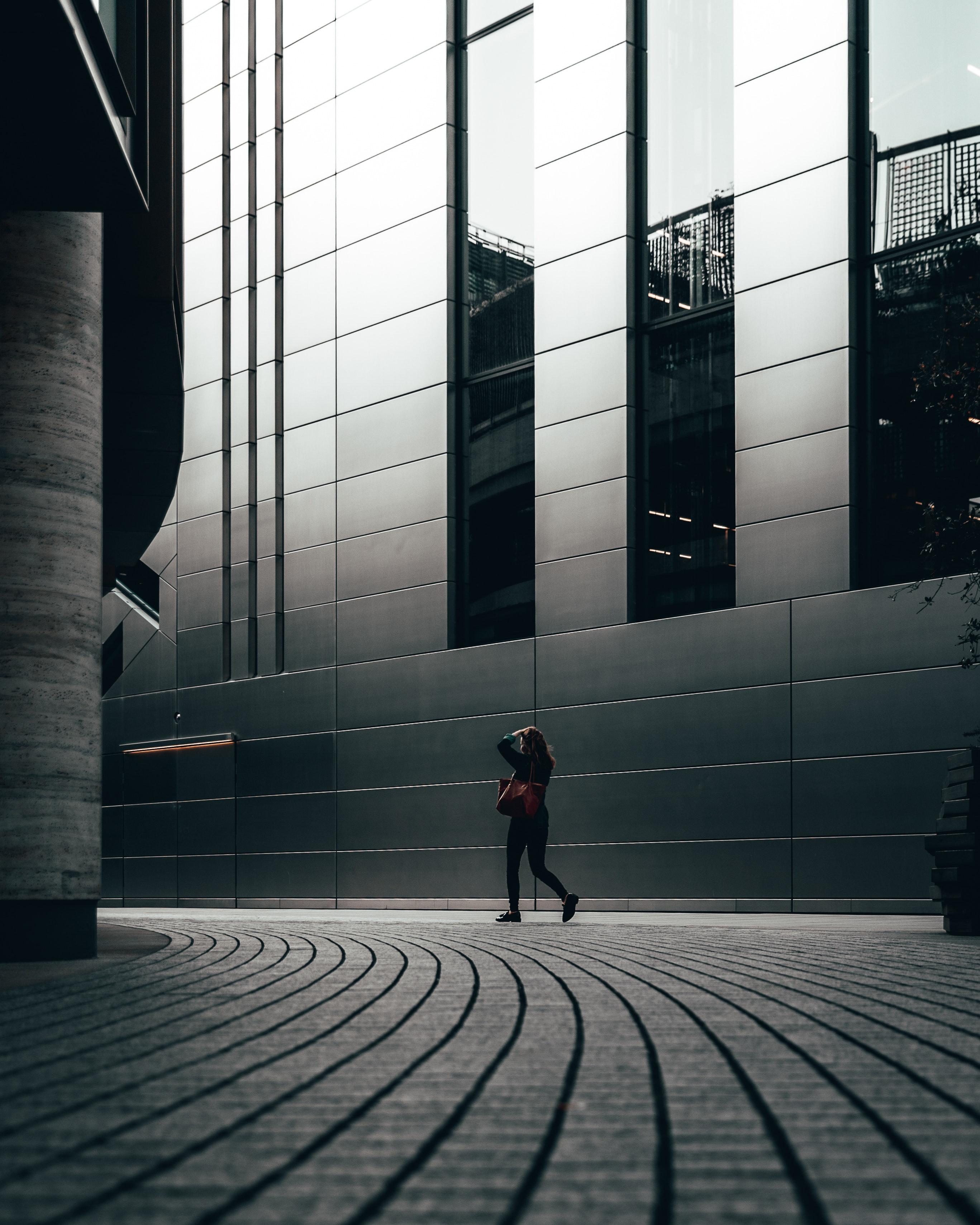 A woman walking beside a building