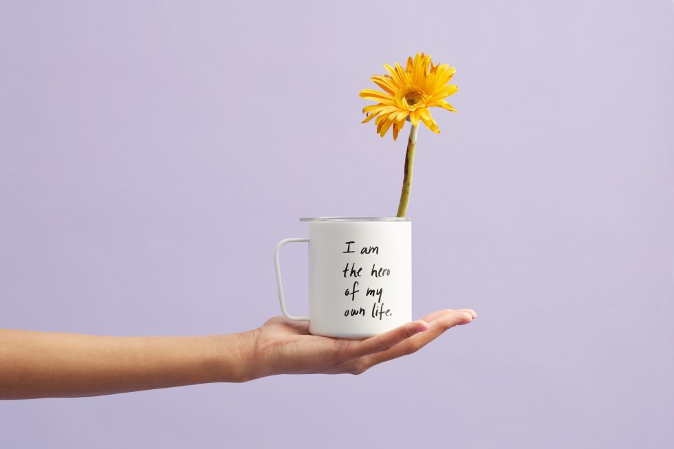 A yellow petaled flower in a white mug in front of a purple wall