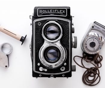 Black Rolleiflex camera on a white surface