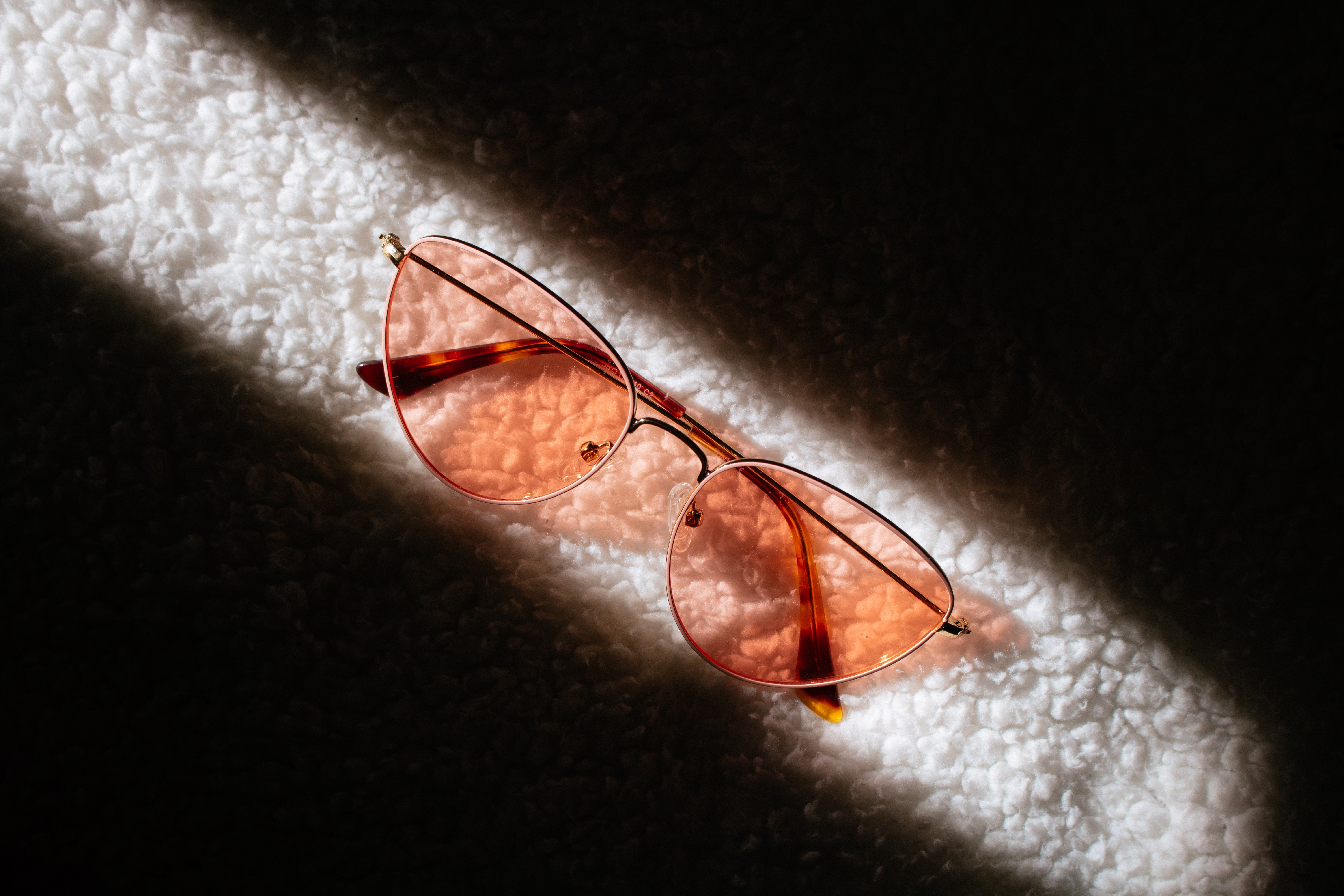 Glasses lying on a white fluffy carpet