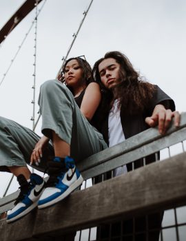 Low-angle photo of a man and woman posing near a rail