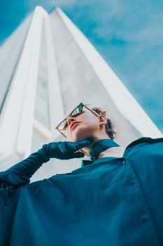 Low-angle photography of a woman in front of a high-rise building