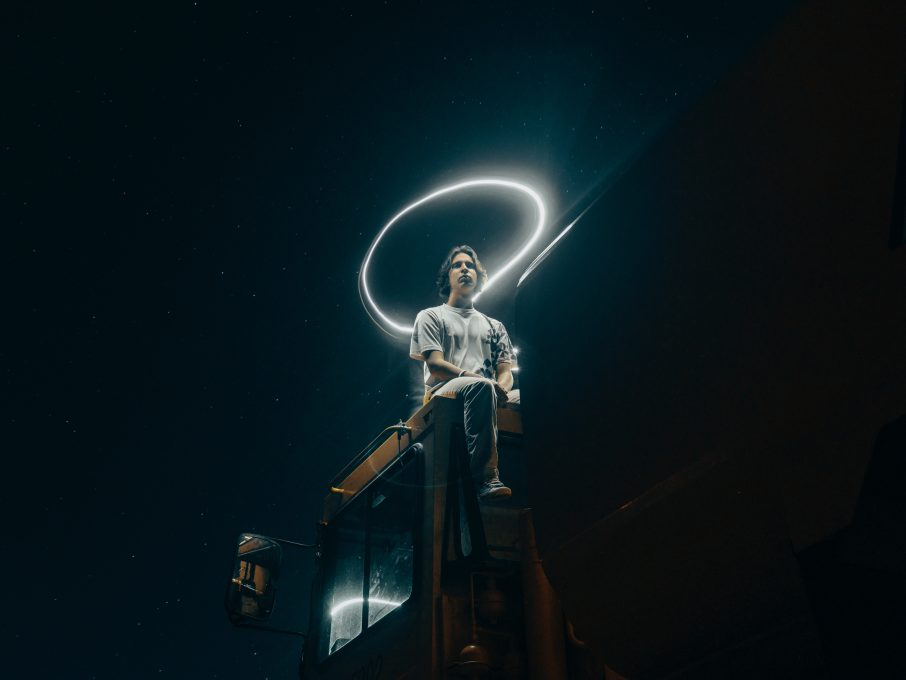 Low-angle shot of a person sitting on a truck's roof at night