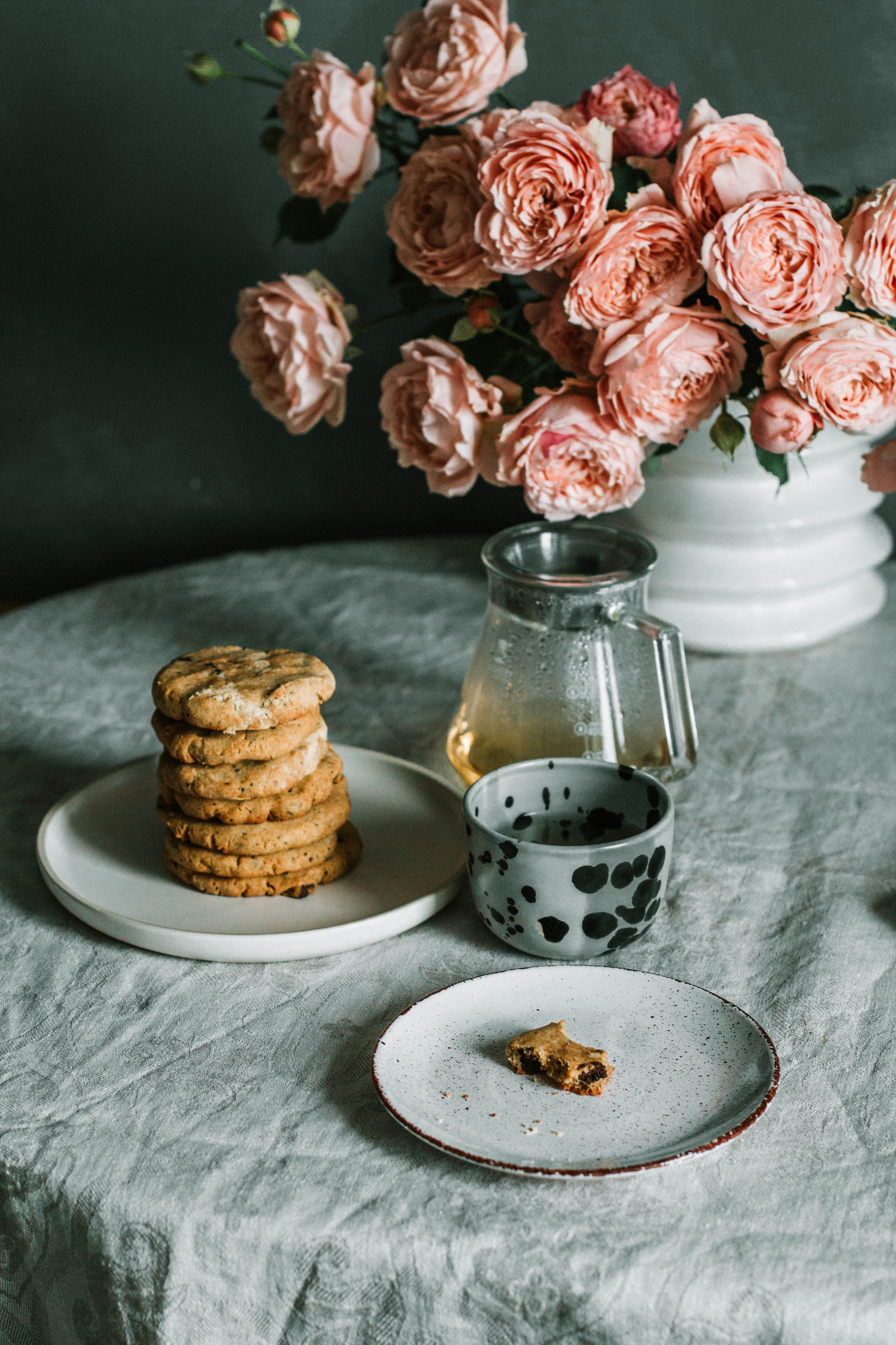 Pink flowers beside a plate of biscuits