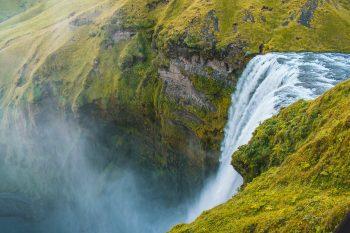 Bird's eye view photo of water falls rushing through cliff