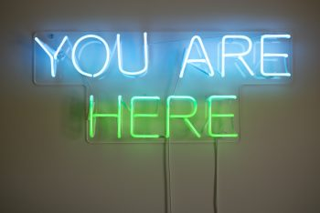 A neon blue and green sign you are here on the wall