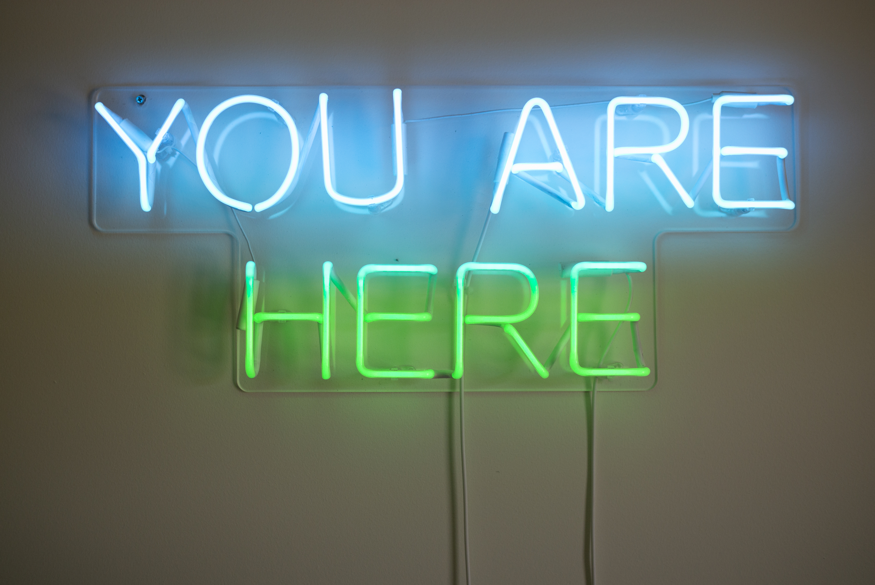 A neon blue and green sign you are here on the wall -pixeor.com