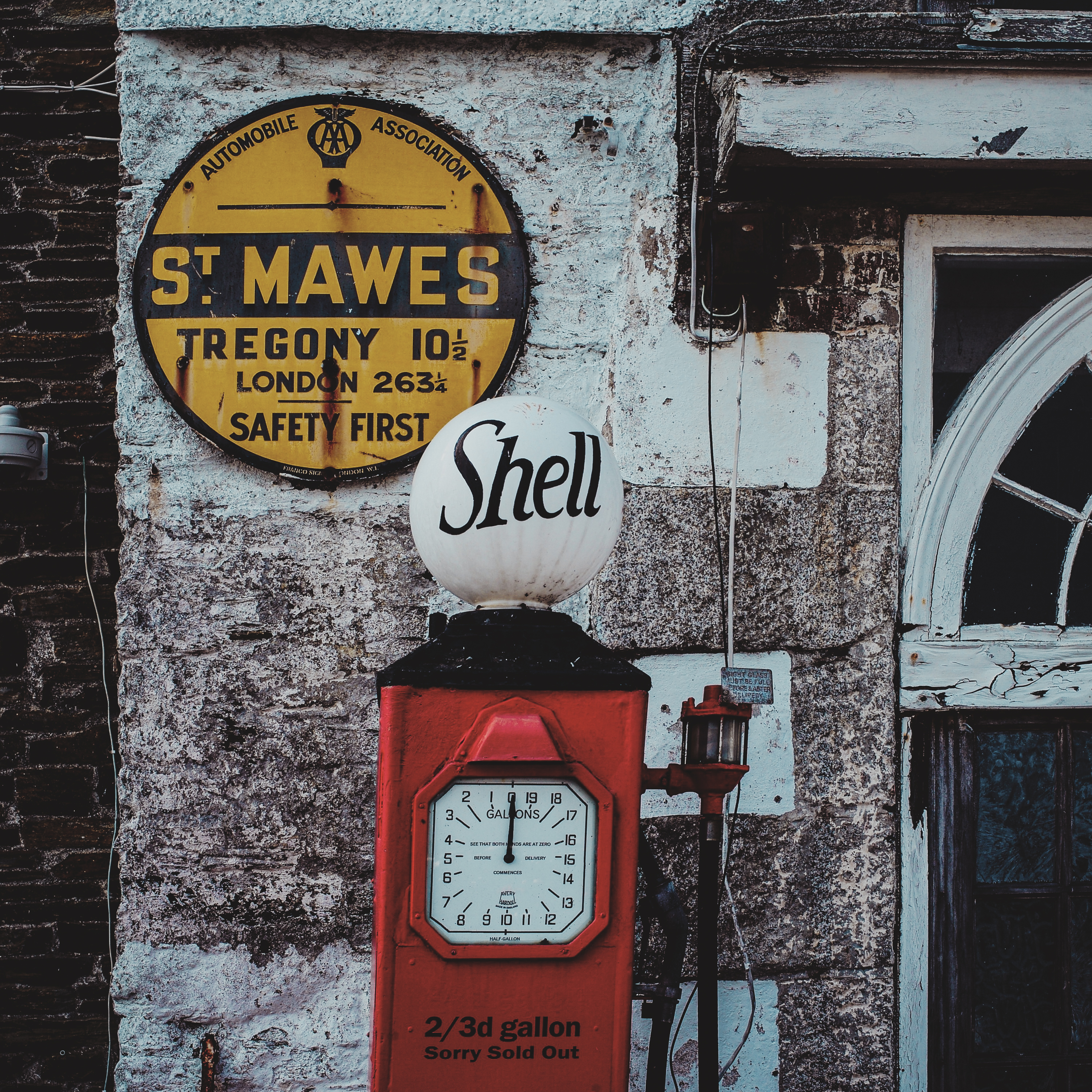 A red petrol pump by an old wall with a yellow sign