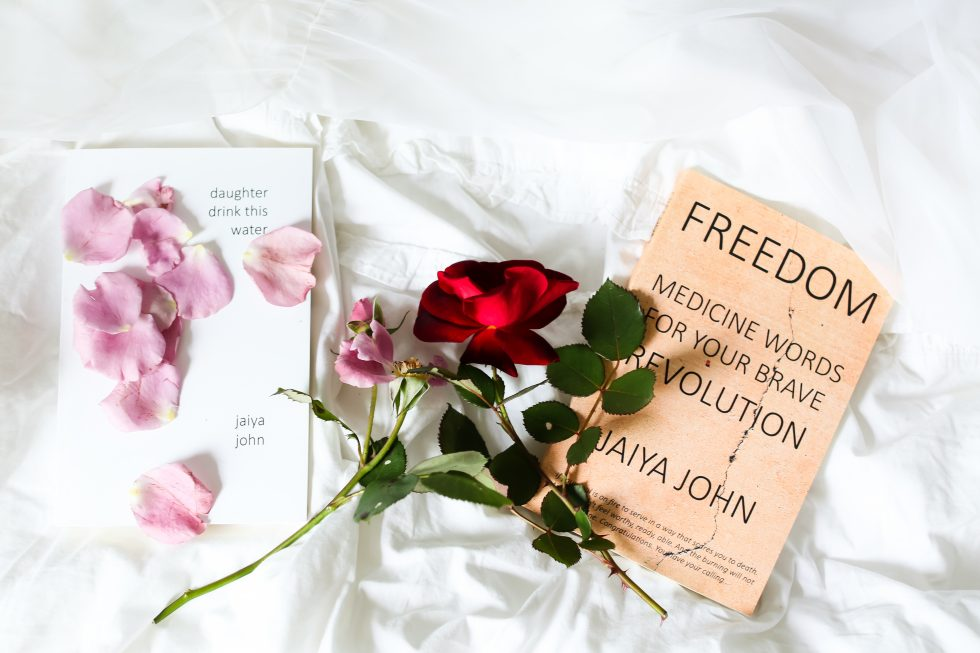A red rose and pink flower with two books lying on white sheets