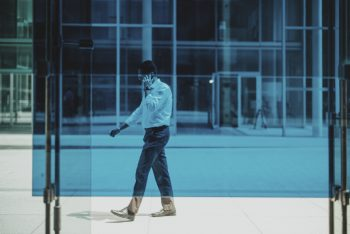 A man walking on the phone behind the glass