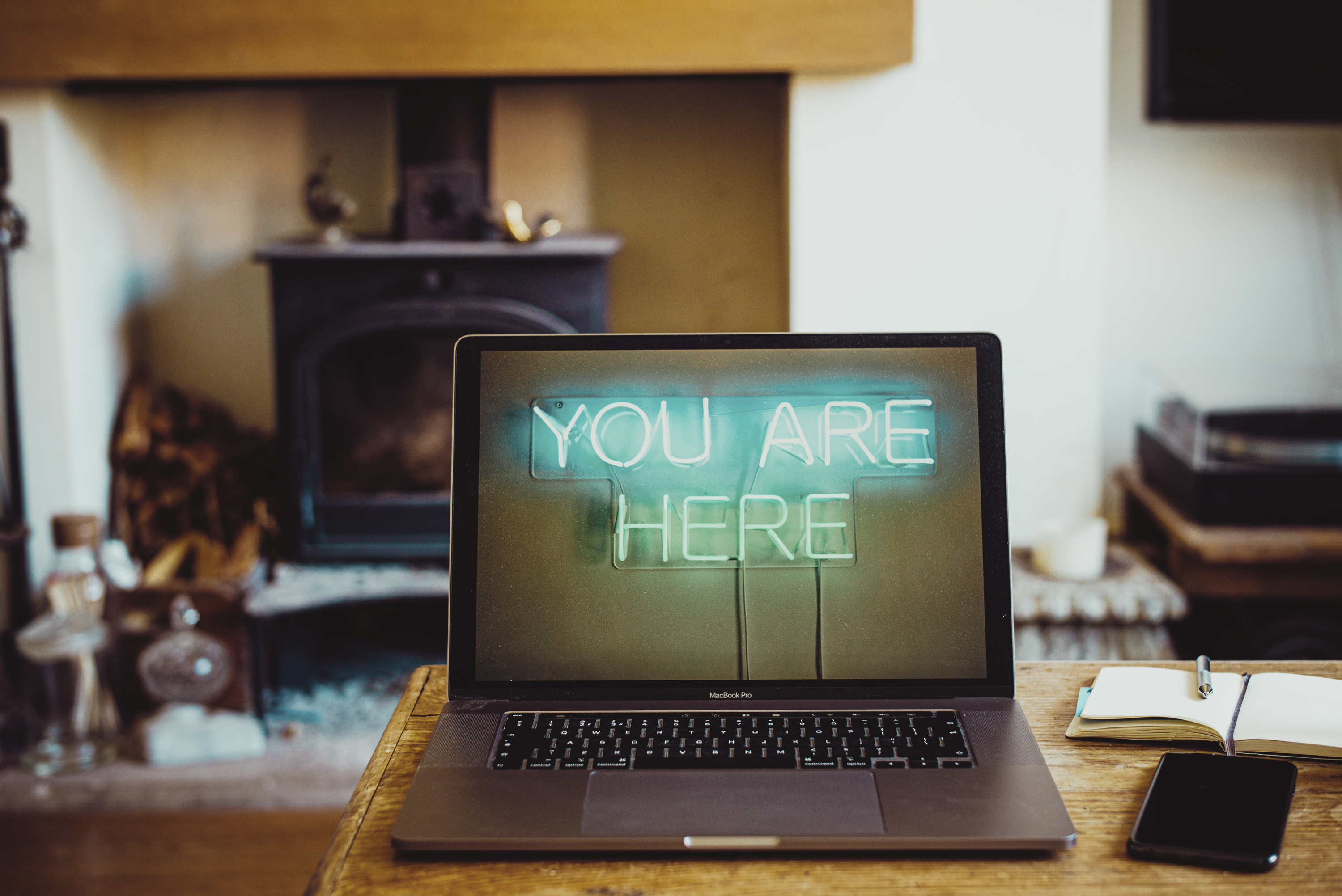 An open laptop with you are here background and notebook with cellphone on a desk