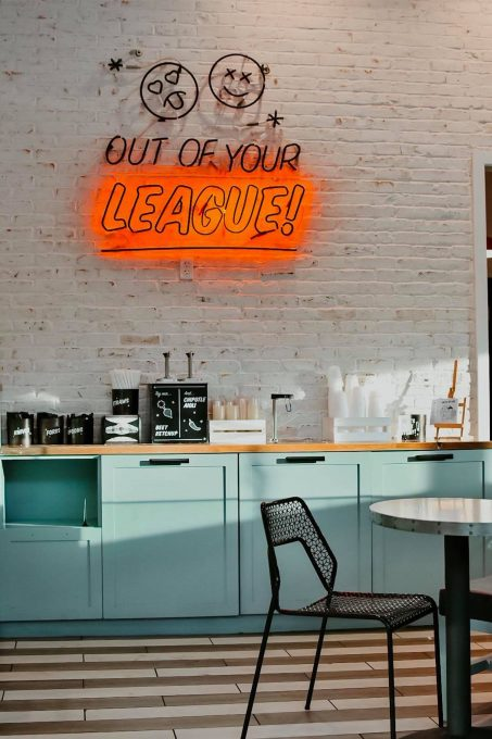 "A coffee counter with a sign ""out of your league"" on the wall"