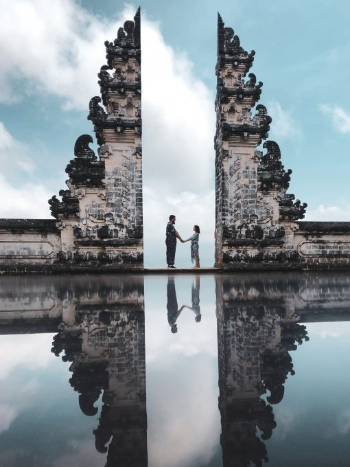 A couple in between of ancient ruins with water reflection