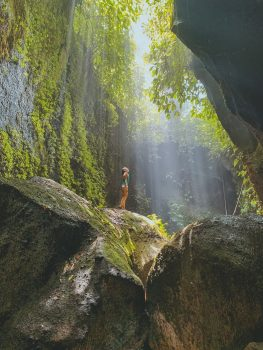 a girl in between rocks and trees
