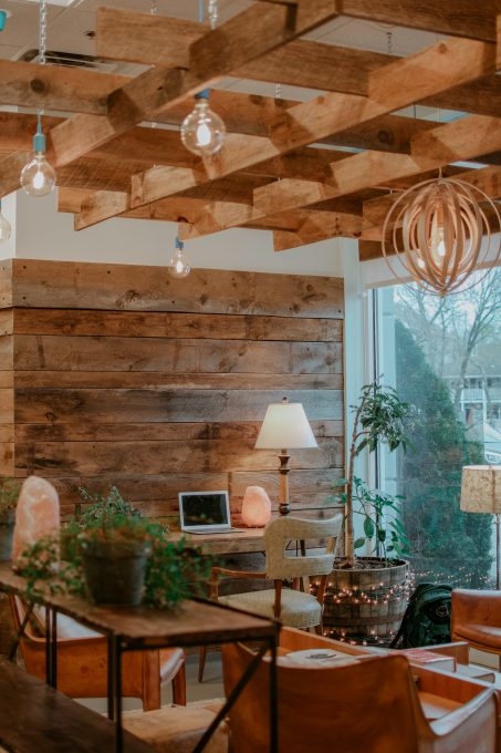 A living room with a wooden wall, desk, chairs, and plants