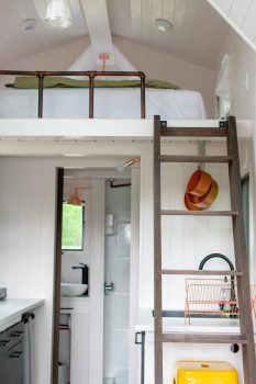 A room with a ladder and a bed