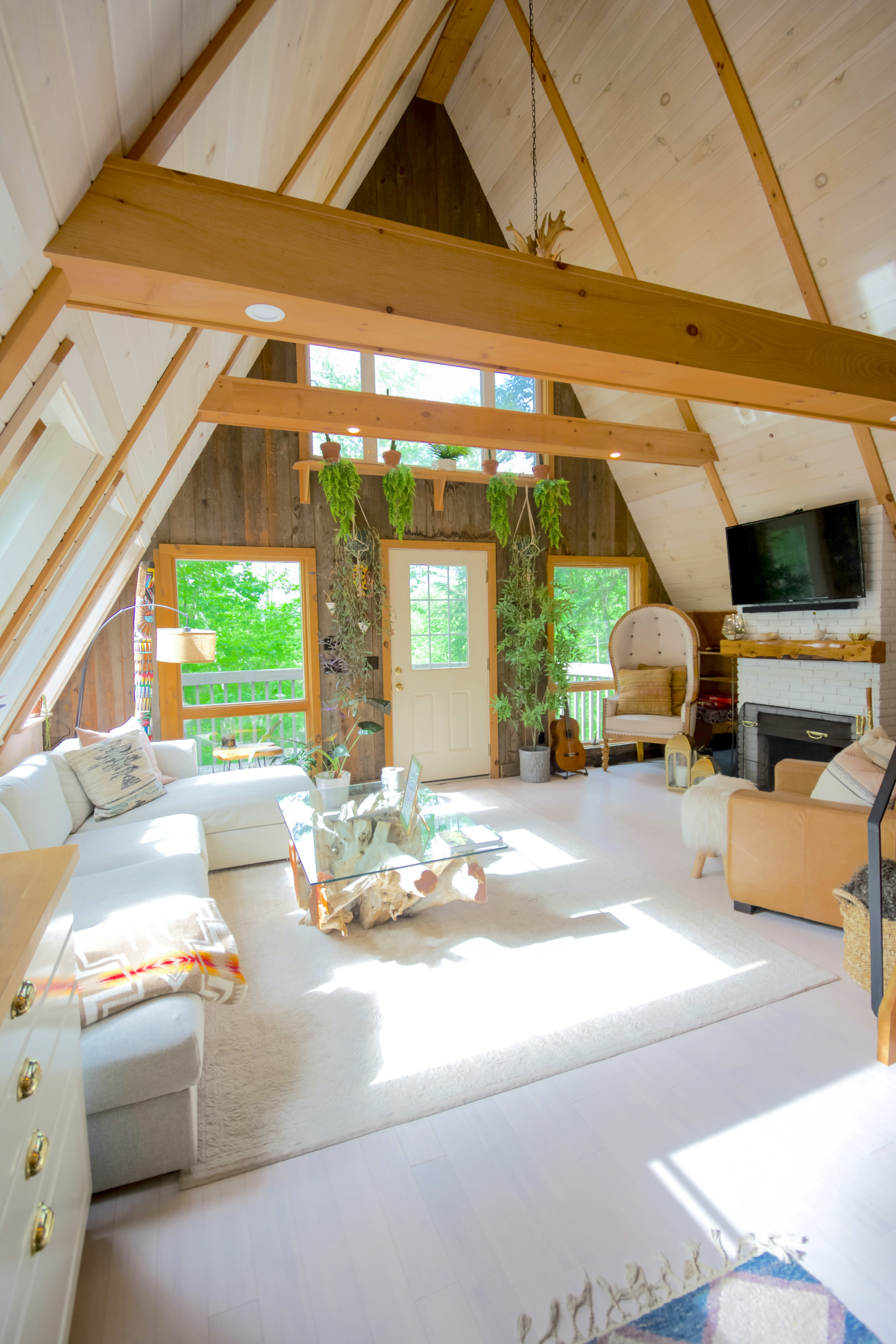 An attic living room with a couch, a tv, chairs